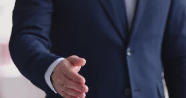 Obchodník v obleku natahuje ruku k fotoaparátu pro potřesení rukou, detailní záběr
