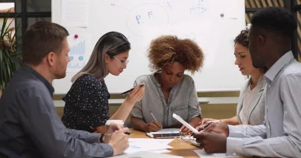 Lächelnde gemischte Geschäftsleute diskutieren Startup-Projekt.