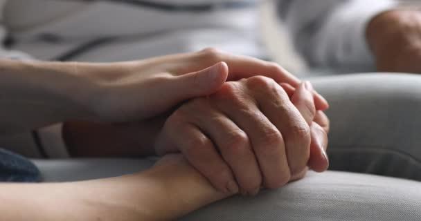 Nahaufnahme junge Frau streichelt Hand der Mutter mittleren Alters.