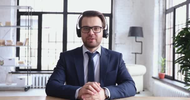 Confident support service representative wears headset talking to webcam