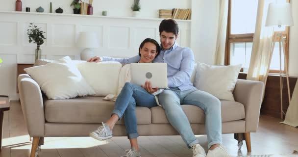 Entspanntes junges Paar mit Laptop auf Sofa im Wohnzimmer