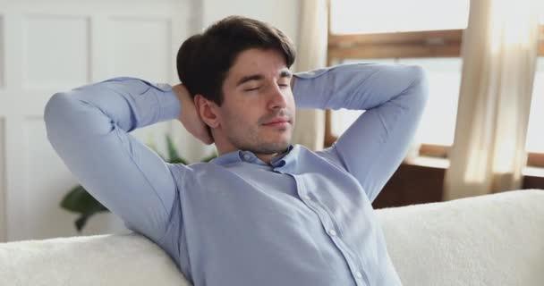 Calm young adult man relaxing in living room on sofa