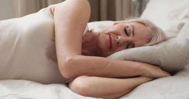 Klidný klidný šťastný dospělý starší žena spí doma.