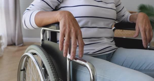 Rentnerin sitzt allein im Rollstuhl zu Hause.