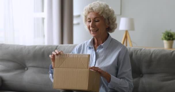 Happy starší starší žena odbalení mezinárodní zásilky.