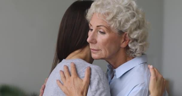 Zamyšlená žena středního věku mazlí se s dospělou dcerou.