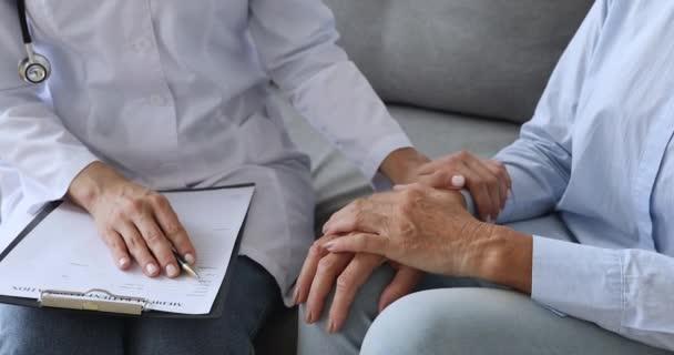 Freundliche Krankenschwester Arzt tröstet ältere Patientin.