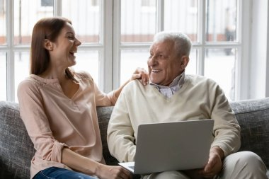 Adult granddaughter and grandfather laughing resting with laptop at home