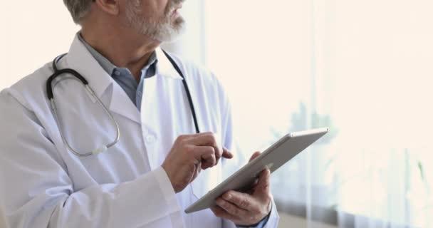 Starý lékař pomocí digitálního tabletu počítače v nemocnici, zblizka