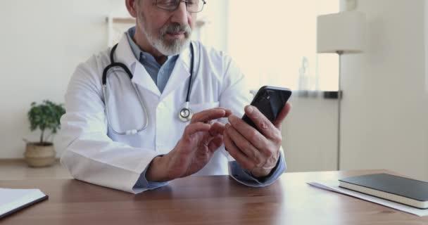 Glücklicher Oberarzt lacht per Smartphone-App am Arbeitsplatz