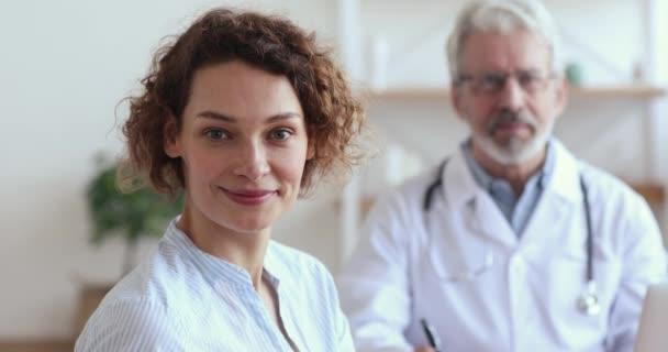 Egészséges, mosolygó európai nő, aki az orvosokat bámulja.
