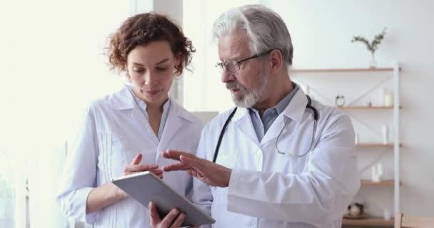Experienced male senior physician holding digital tablet teaching female nurse