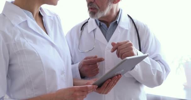 Ärzteteam zwei Ärzte mit Tablette, Händeschütteln, Nahaufnahme