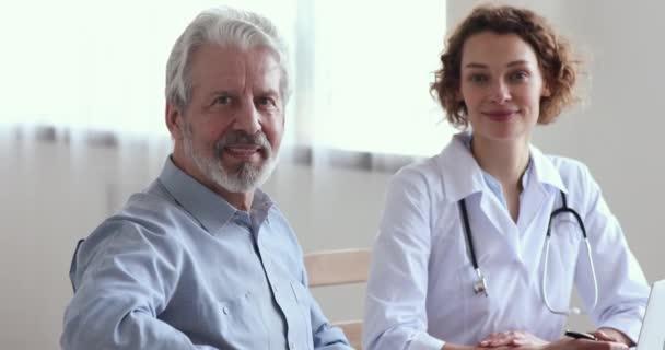 Lächelnde Seniorin besucht Ärztin und schaut in Kamera