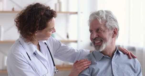 Caring kind female doctor embracing reassuring happy senior patient