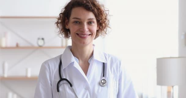 Lächelnde Kardiologin zeigt Herz beim Blick in die Kamera