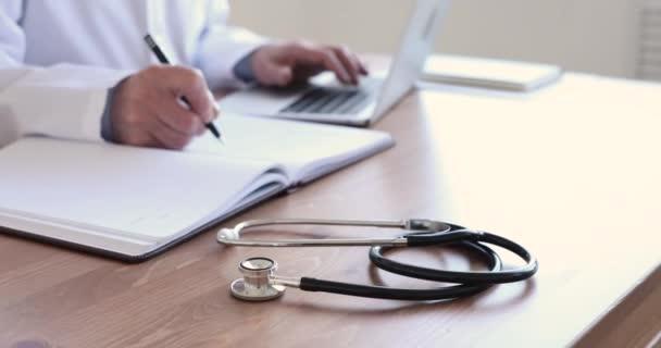 Starší lékař pracující u stolu lékařské ordinace se stetoskopem
