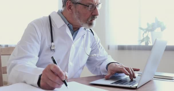 Serious old therapist doing online research making notes in journal