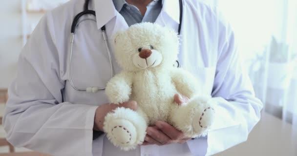 Oberarzt für Allgemeinmedizin mit Teddybär in der Hand, Nahaufnahme