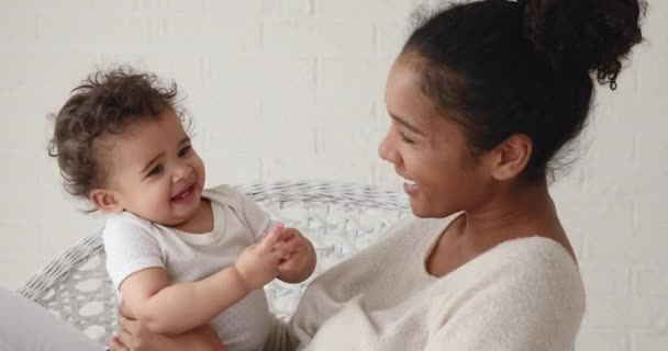 Sweet mixed race infant boy clapping hands playing with mom