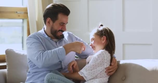 Happy young bearded father tickling small school aged child daughter.