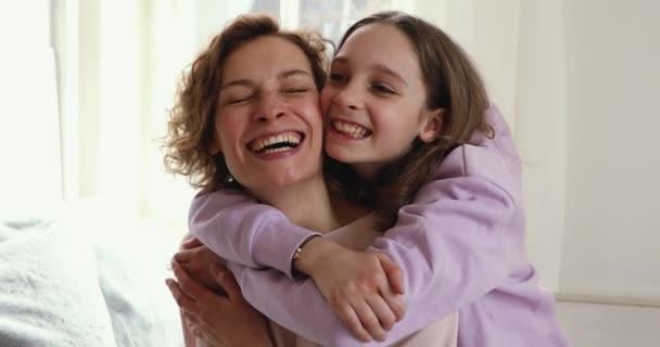 Schön lächelnd Teenager-Tochter umarmt Mutter Blick in die Kamera