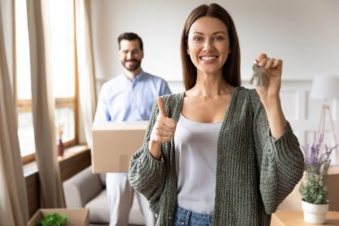 Overjoyed young 30s woman holding keys, showing thumbs up gesture.