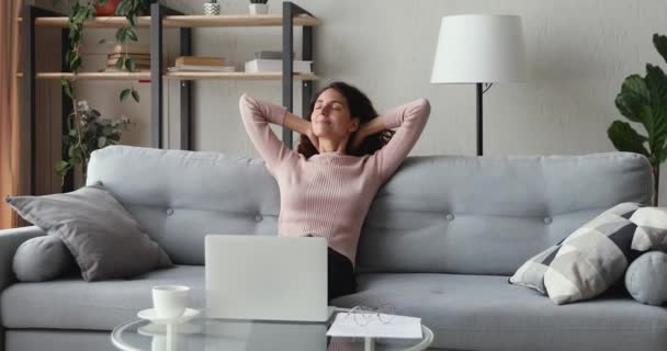 Happy woman freelancer relaxing from computer work sitting on sofa