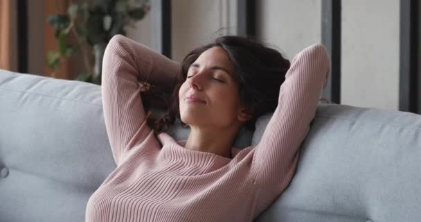Happy relaxed single lady resting on comfortable sofa at home