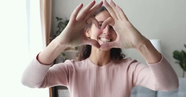 Usmívající se mladá žena ukazuje srdce při pohledu do kamery, portrét