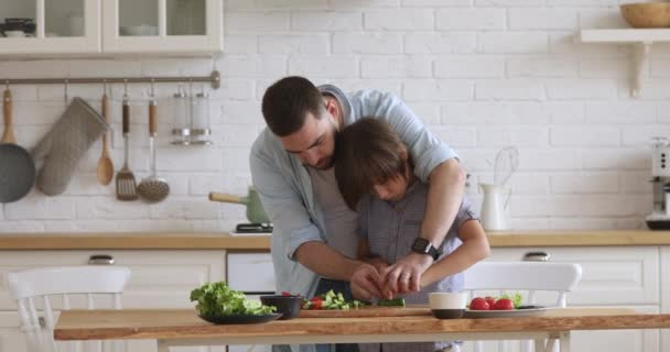 Young father teaching kid son cutting vegetable salad in kitchen