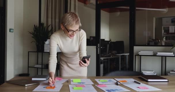 Geschäftsfrau mit Smartphone kommuniziert per Videokonferenz