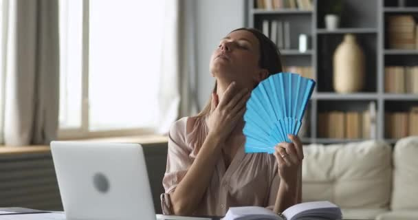 Stressed young woman using fan, suffering from high temperature inside.