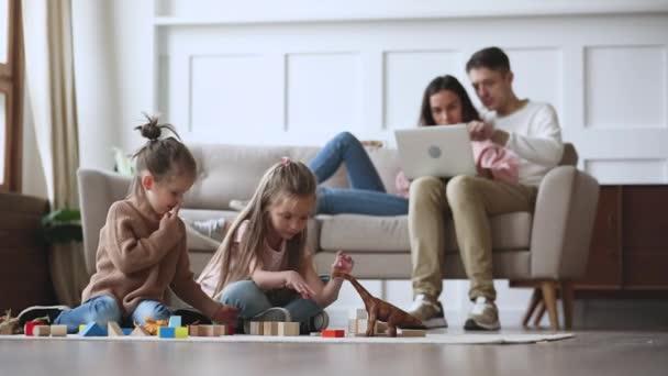 Malé děti hrají hračky, zatímco rodiče používají počítač.