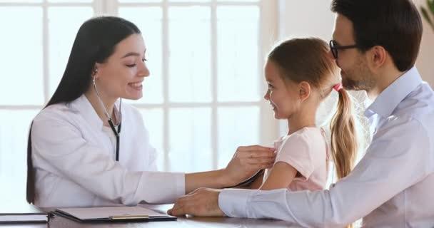 Lächelnde freundliche Kinderärztin hört Herzschlag eines glücklichen Vorschulkindes.