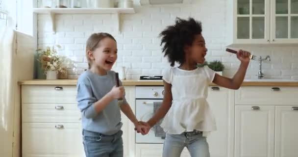 Šťastné africké a kavkazské děti nevlastní sestry zpěv, tanec v kuchyni