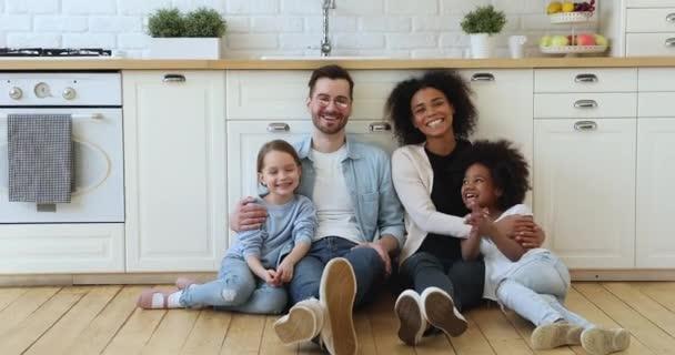 Šťastný smíšený závod rodina sedí na podlaze v kuchyni doma