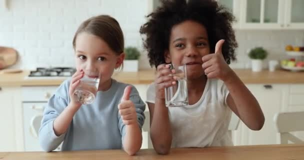 Two funny mixed race children drinking water showing thumbs up
