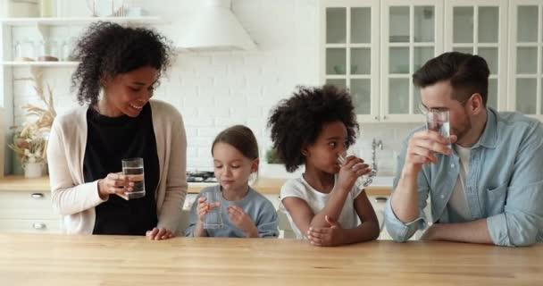Šťastný zdravý smíšené rasy rodina pitná voda ukazující palce nahoru
