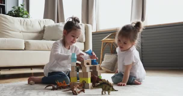 Two adorable kids sisters playing wooden blocks sitting on floor