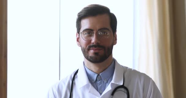 Mladý usměvavý muž praktický lékař v brýlích při pohledu do kamery.