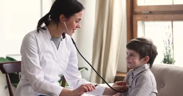 Junge Kinderärztin hört Lungen einer kleinen entzückenden Patientin zu.