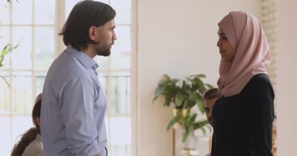Confident male team leader shaking hands praising female arabic colleague.