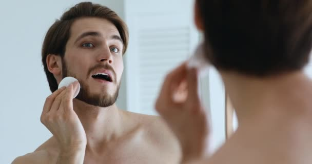 Handsome man holding pad cleansing face skin looking in mirror