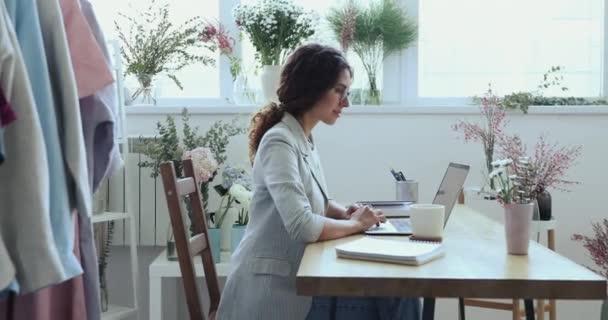 Mosolygós nő professzionális divattervező segítségével laptop nézi kamera