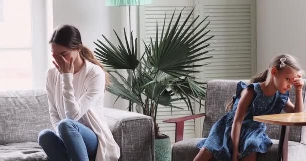 Gestresste junge Mutter sitzt getrennt von Tochter auf Sofa.