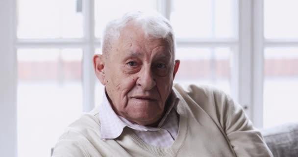 Šťastný starší muž se zdravými bílými zuby při pohledu do kamery.