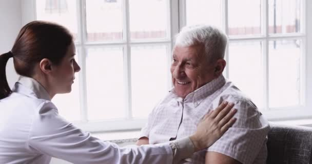 Young female general practitioner touch shoulder of smiling elderly patient.
