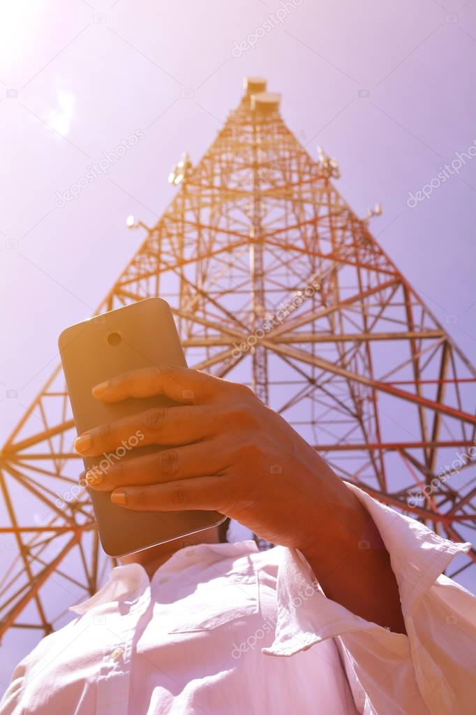 Woman with smartphone near telecommunication tower