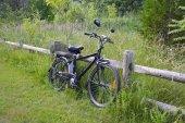 Fotografie Elektro-Fahrrad auf dem Holz Zaun